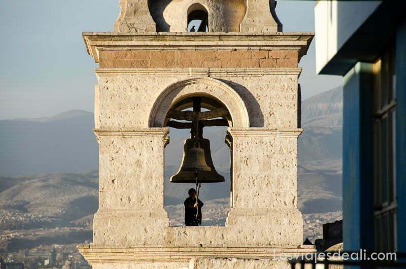 señora tocando a misa en un campanario