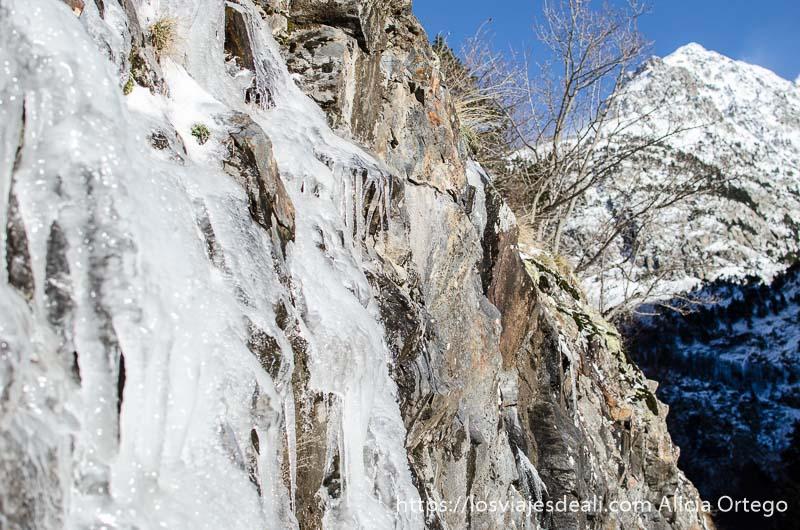 cascada congelada y pico nevado al fondo con cielo muy azul