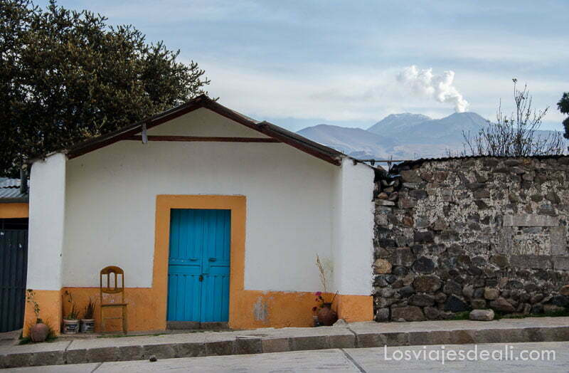 casita blanca y amarilla con silla de madera junto a la puerta y al fondo volcán con fumarola