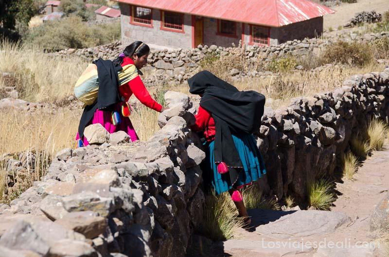 una mujer vestida de colores ayuda a otra a pasar por valla de piedra