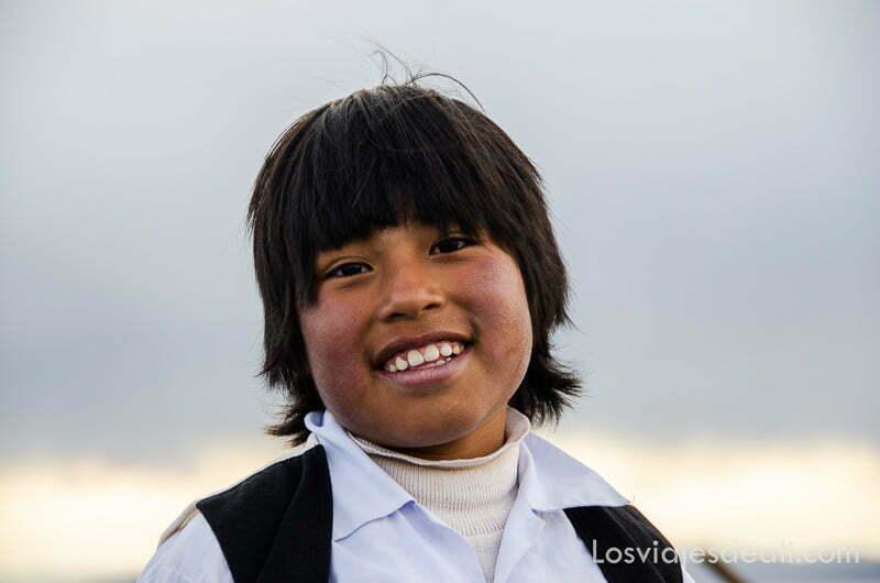 niño sonriente con flequillo y chaleco negro