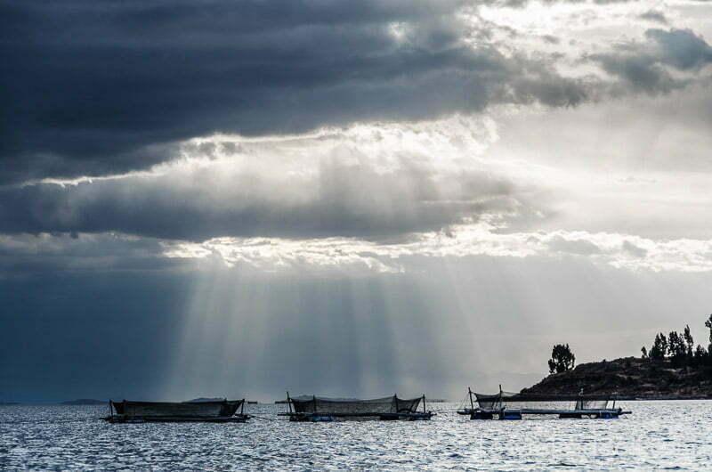 redes de pesca en el lago titicaca con grandes nubarrones y rayos de sol atravesándolos como una cortina
