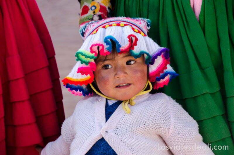 niña de un año y medio con chaqueta de lana blanca y gorro de lana blanca con ribetes de colorines