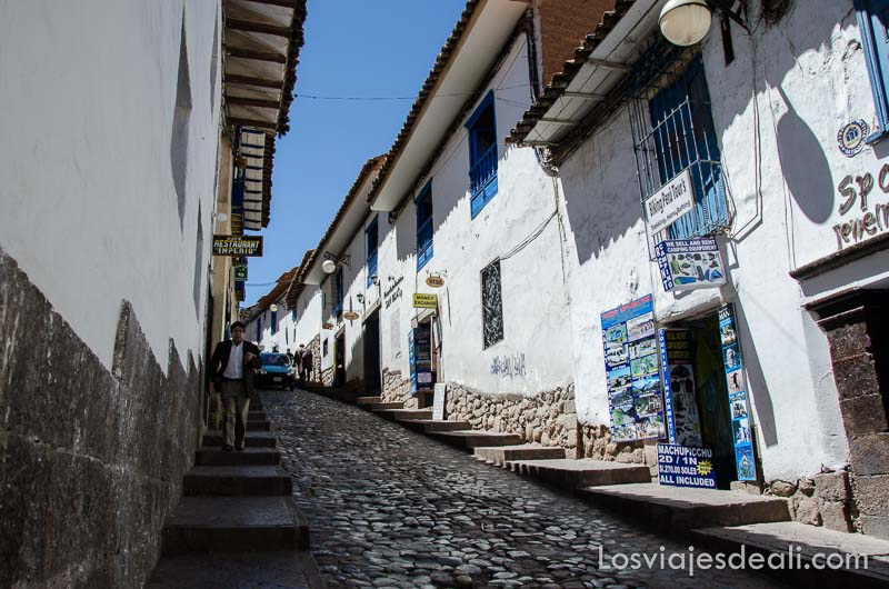 calle empedrada en cuesta con casas encaladas y ventanas azules