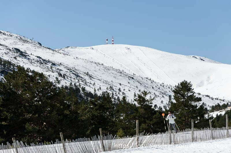 chica haciendo esquí de fondo junto a valla que marca la pista y detrás montaña nevada