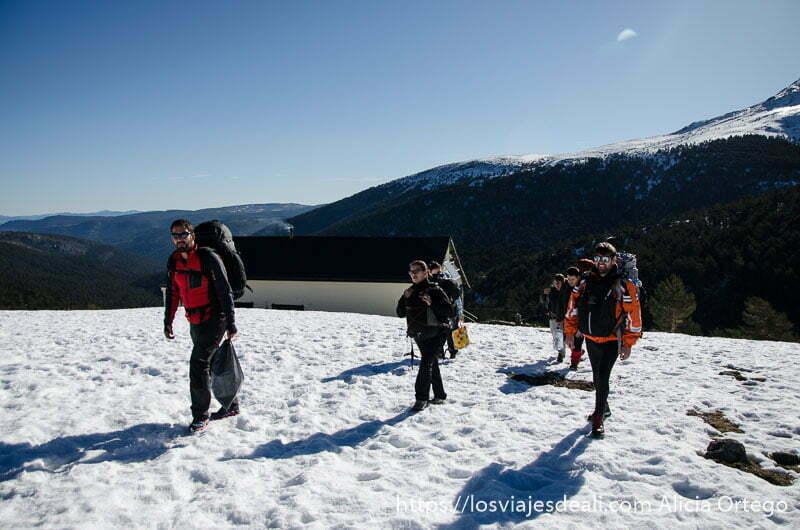 compañeros de viaje con las mochilas andando sobre la nieve