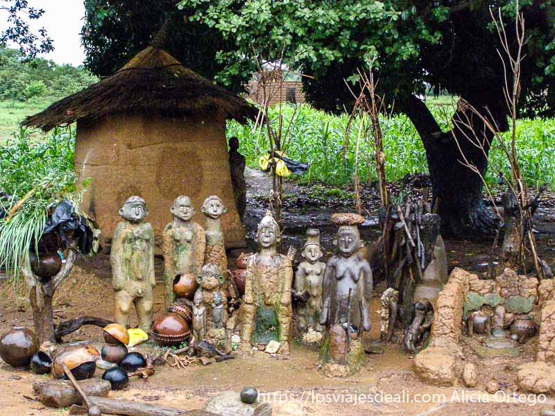 muñecos de barro con ojos de conchas delante de  una casa en el país lobi