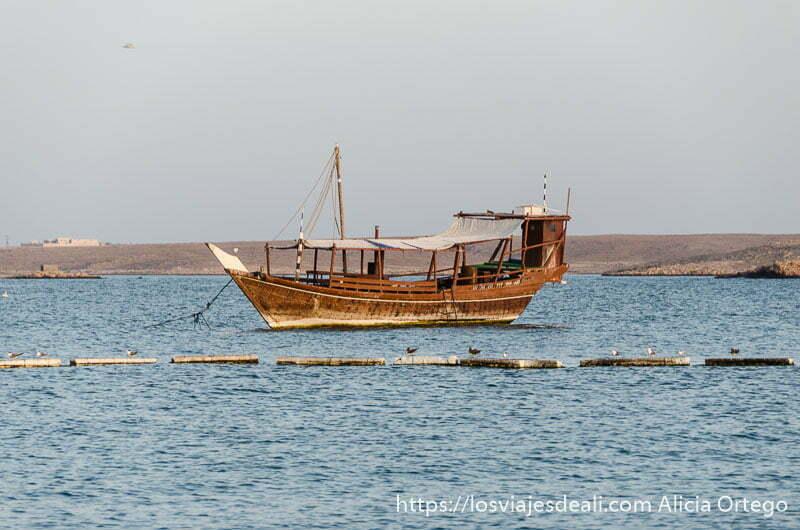dhow de madera anclado en el agua cerca de la playa