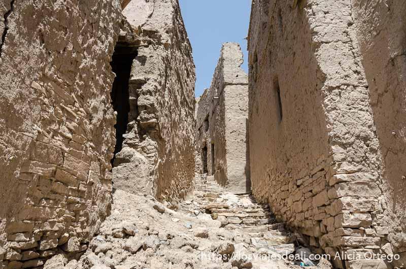 calle de pueblo en ruinas con casas de adobe y escaleras de piedra