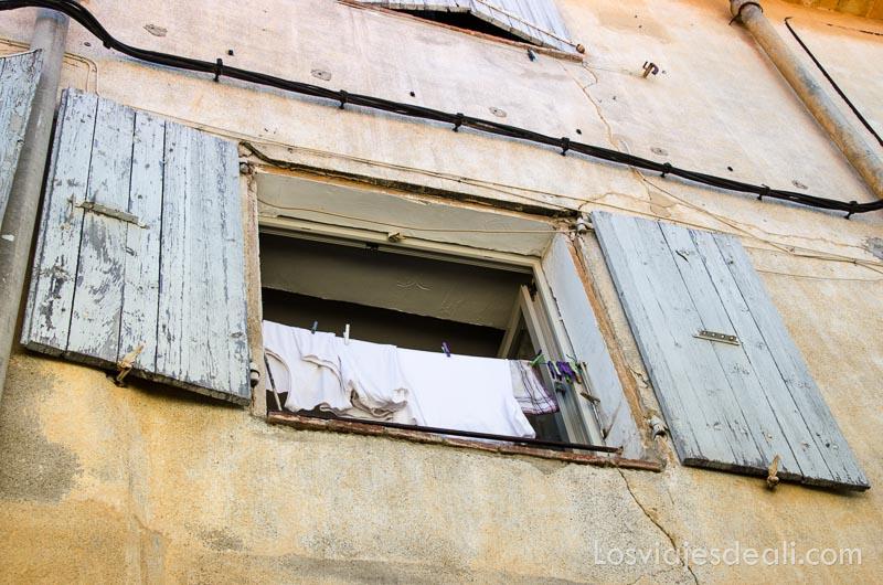ventana abierta con ropa blanca tendida