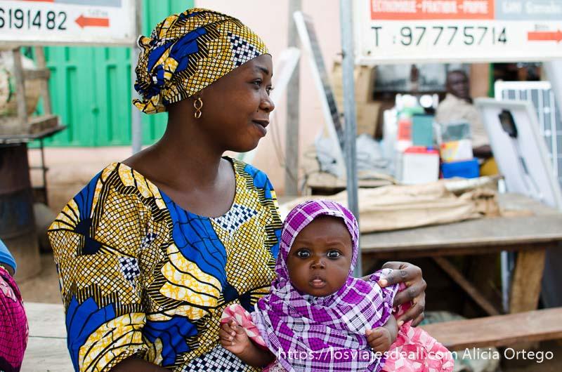 mujer africana con su bebé en el regazo que mira fijamente a la cámara vestidas con telas de colores