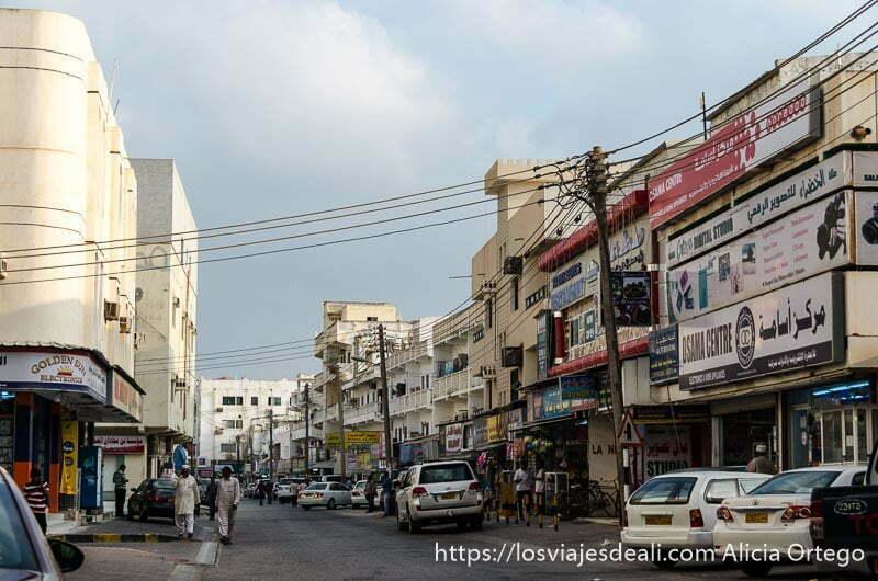 calle de salalah con edificios modernos llenos de carteles y cables que cruzan por encima