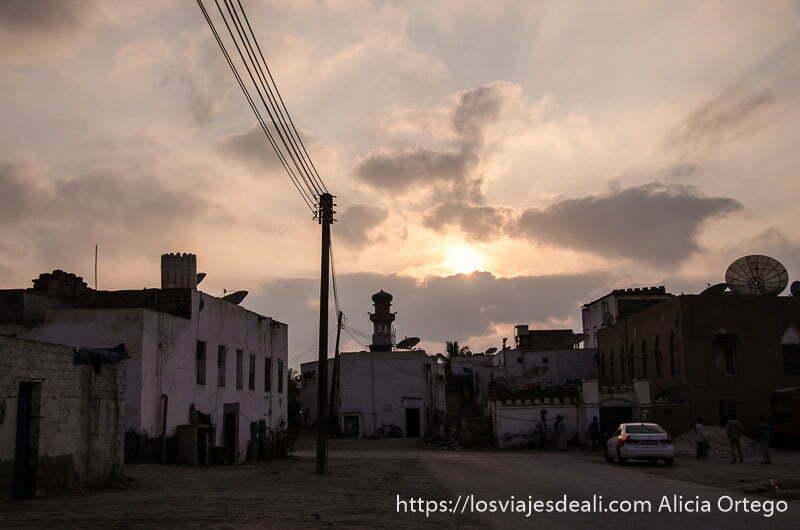 puesta de sol con nubes y una mezquita recortándose al fondo en las calles de salalah