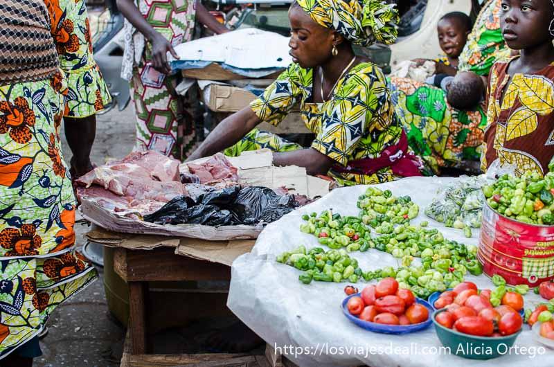 mujer despachando carne en un mercado de benin