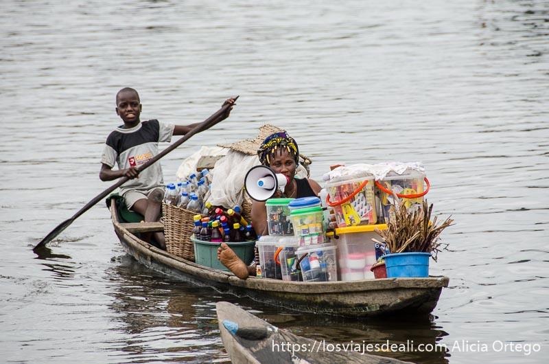 mujer con megáfono en su barca llena de mercancías y niño impulsando la barca con una pértiga en ganvie