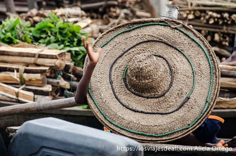 niño tapándose con gran sombrero de paja y saludando con la mano en ganvie