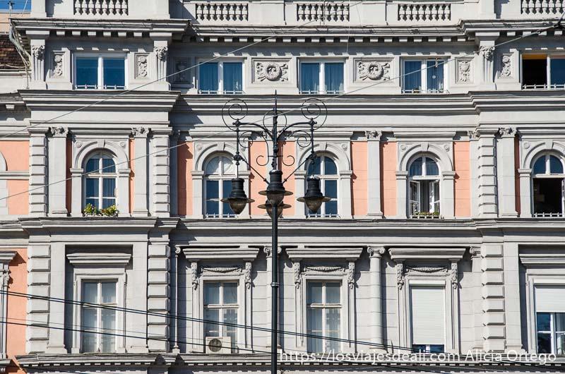 fachada señorial con ventanas y farola de hierro y cables de tranvía delante calles de budapest