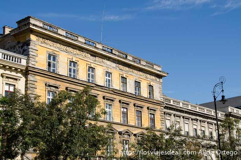 edificio señorial pintado de amarillo destacando en cielo azul calles de budapest