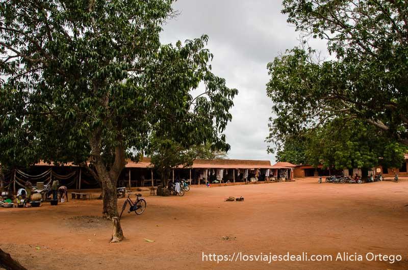 patio principal del palacio de abomey con piso de tierra roja y dos grandes árboles patrimonio de la humanidad de benin