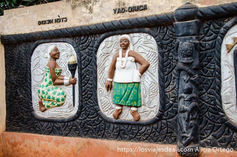 relieves en un muro de un templo vudú representan mujeres pintadas de colores patrimonio de la humanidad de benin