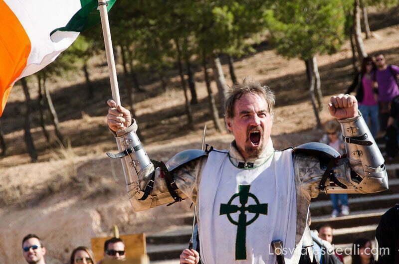 guerrero de irlanda levantando los puños y gritando con la bandera en la mano torneo internacional de combate medieval