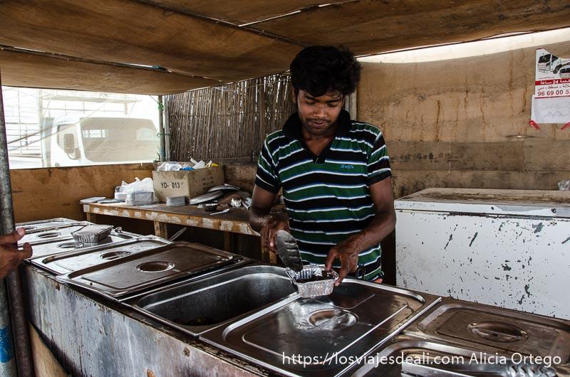 chico sirviendo arroz y carne para llevarnos de picnic visitas que hacer cerca de salalah