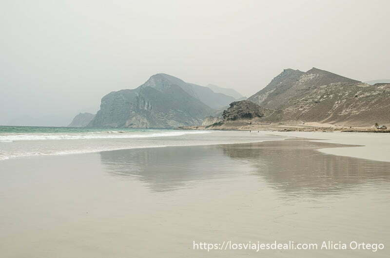 playa con dos montañas reflejándose en la arena mojada visitas que hacer cerca de salalah