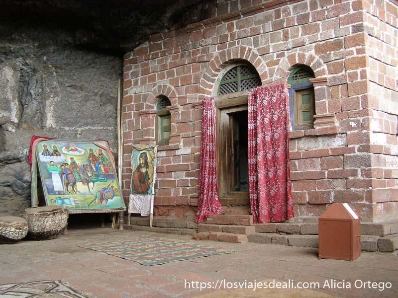 patio de la iglesia con cortinas en la puerta y un cuadro de jesucristo al lado iglesias de etiopía