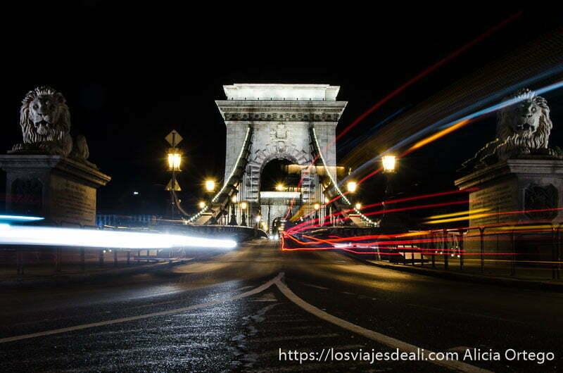 puente de las cadenas por la noche con luces de coche y autobús como si fueran líneas de colores