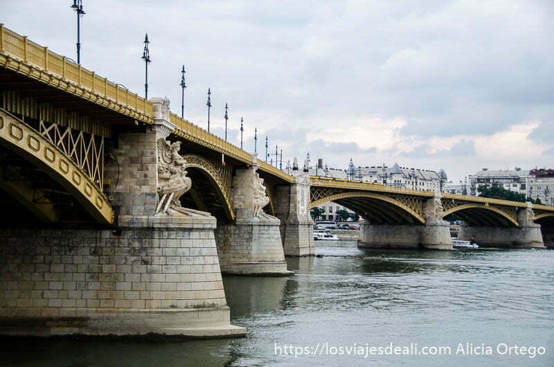 puente de margarita con la forma de ángulo y estatuas de mujeres en los apoyos de los arcos puentes de budapest