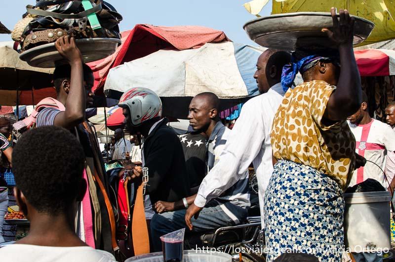 gente pasando con bandejas en la cabeza y una moto con dos hombres en el mercado de la capital de togo