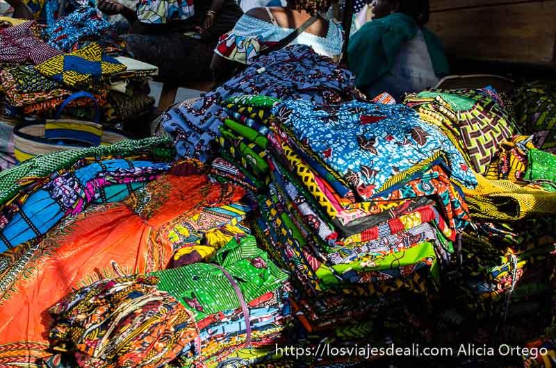 telas africanas con estampados de colores apiladas en el mercado de la capital de togo