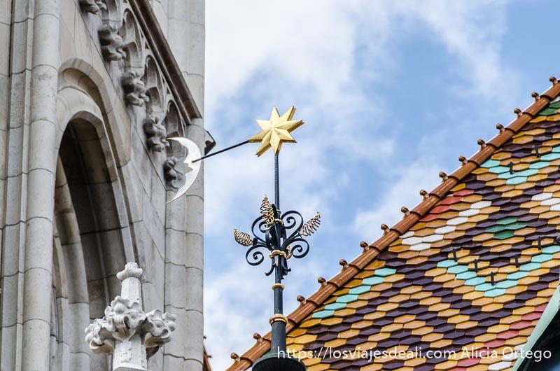 veleta con el sol y la luna junto al tejado de tejas de colores guía del budapest monumental