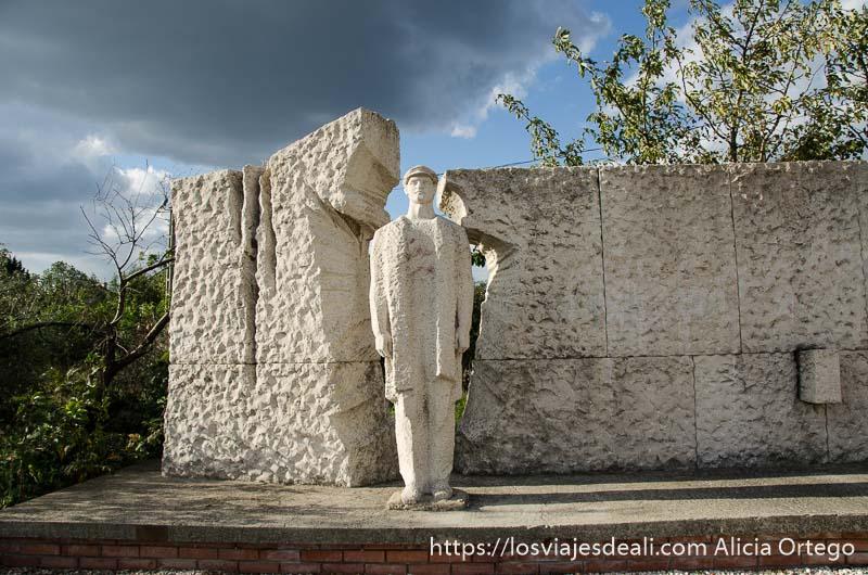 estatua de piedra de lenin como saliendo de una pared de la misma piedra pasado comunista de budapest
