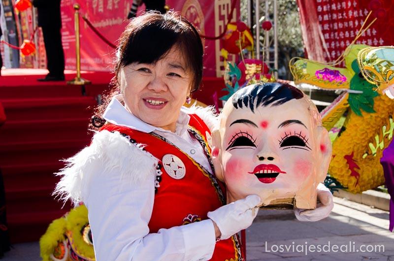 mujer sosteniendo una cabeza de papel maché en el año nuevo chino en madrid
