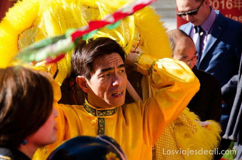 hombre saliendo de debajo de un dragón amarillo en el año nuevo chino en madrid