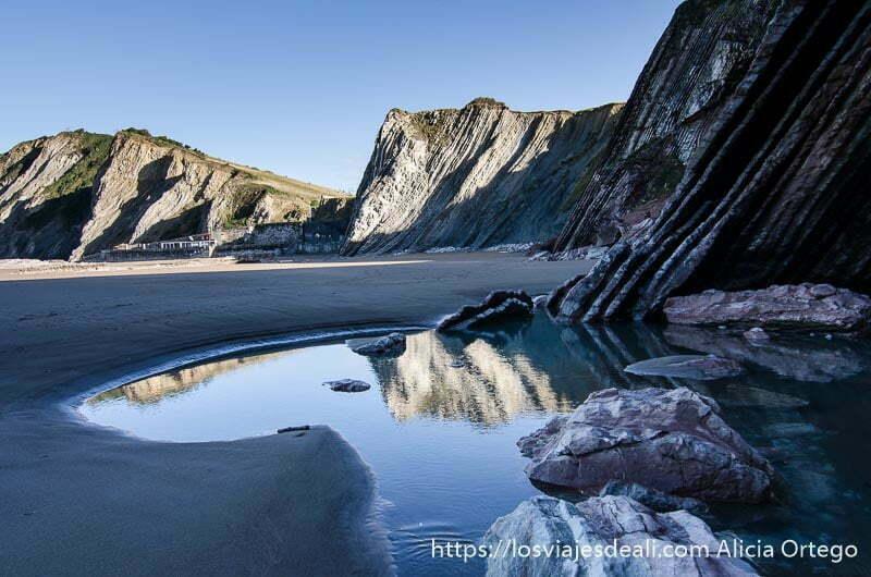 playa con charco donde se reflejan acantilados del flysch