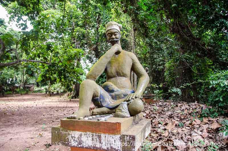 escultura de hombre sentado con mano apoyada en barbilla en bosque sagrado de ouidah