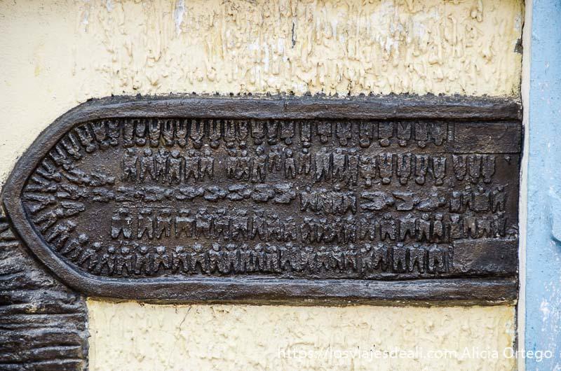 relieve en una pared con forma de barco y los esclavos que viajaban en él en ouidah benin