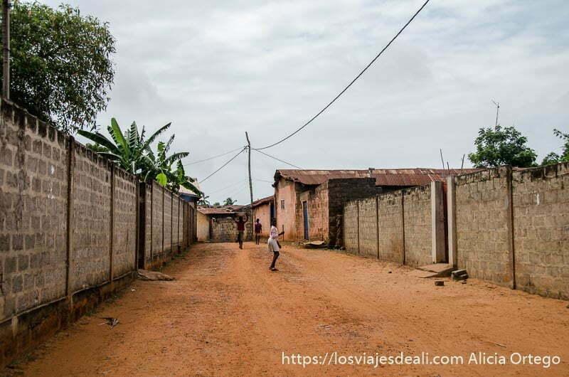 calle de tierra roja con muros a los lados en ouidah benin