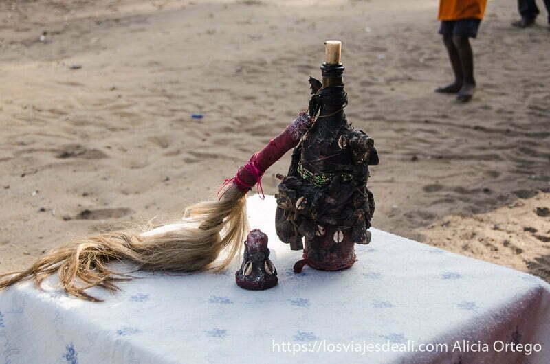 botella de licor sobre mantel blanco en la ceremonia vudú
