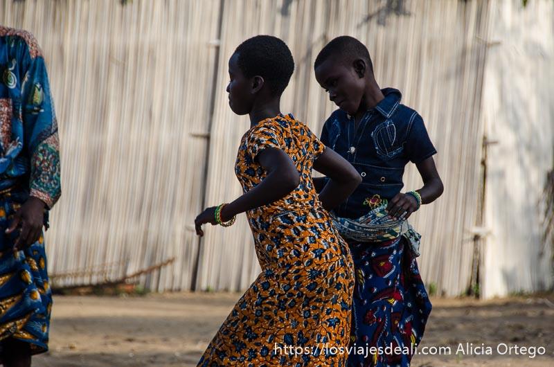dos niñas de 11 o 12 años bailando juntas en la ceremonia vudú