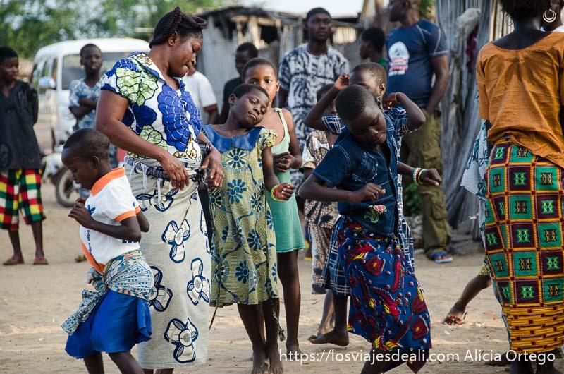 mujer rodeada de niñas bailando en la ceremonia vudú
