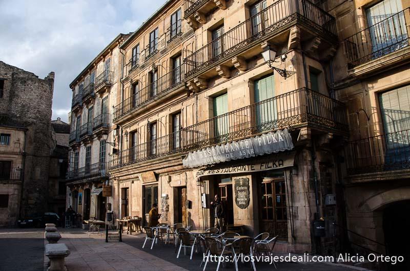 casas de plaza mayor con balcones y restaurante iluminadas por sol de atardecer