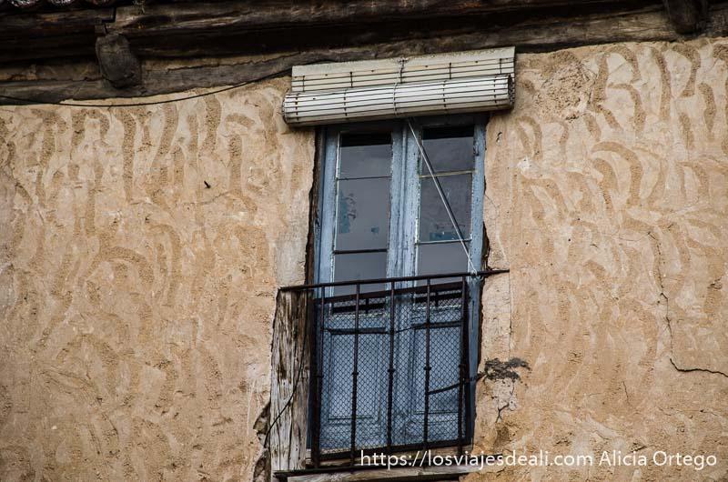 ventana de madera con balcón de hierro en pared revocada a mano en sepúlveda