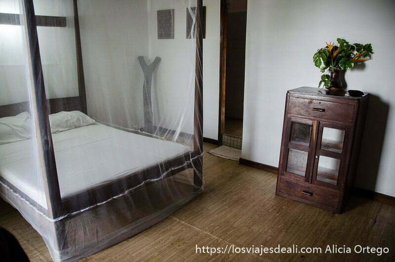 habitación de hotel aubergue con cama con palio y mosquitera y cómoda de madera junto a una de las playas de benin