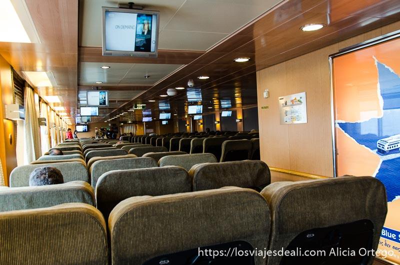 filas de asientos con televisor dentro de un ferry grecia en temporada baja