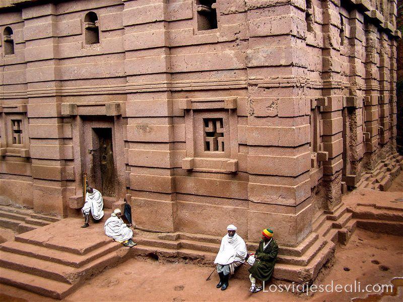 4 hombres con sus mantas sentados en puerta de iglesia excavada en la roca iglesias de lalibela