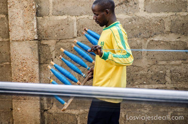 hombre llevando varios rollos de hilo azul extendiéndolos para el telar en bafiló ruta por el interior de togo