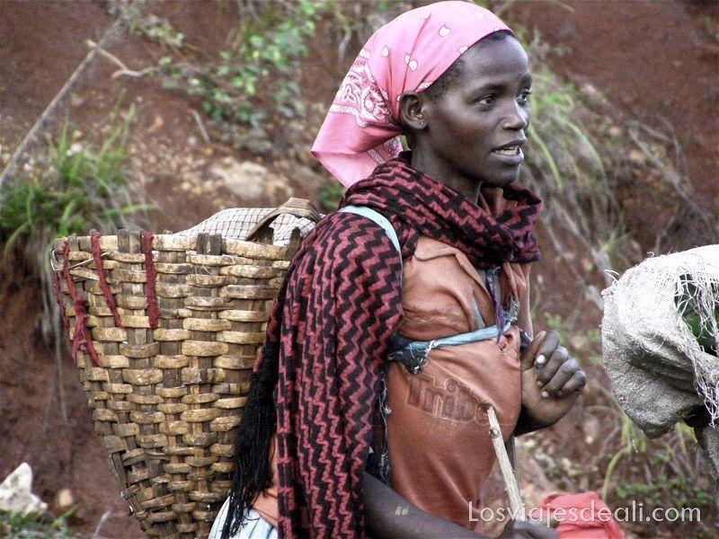 mujer etíope con pañuelo rosa en la cabeza y gran cesto a la espalda